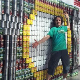 Unicycle Creative Lorne Craig poses with Canstruction sculpture